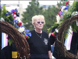 Sharon Machcinski, mother of firefighter Stephen Machcinski, looks at the wreath placed for her son during the Toledo Fire Department's annual memorial service.