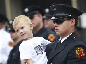 Gavin Getzinger, 4, left, is held by his father Kyle Getzinger during the Toledo Fire Department's annual memorial service.