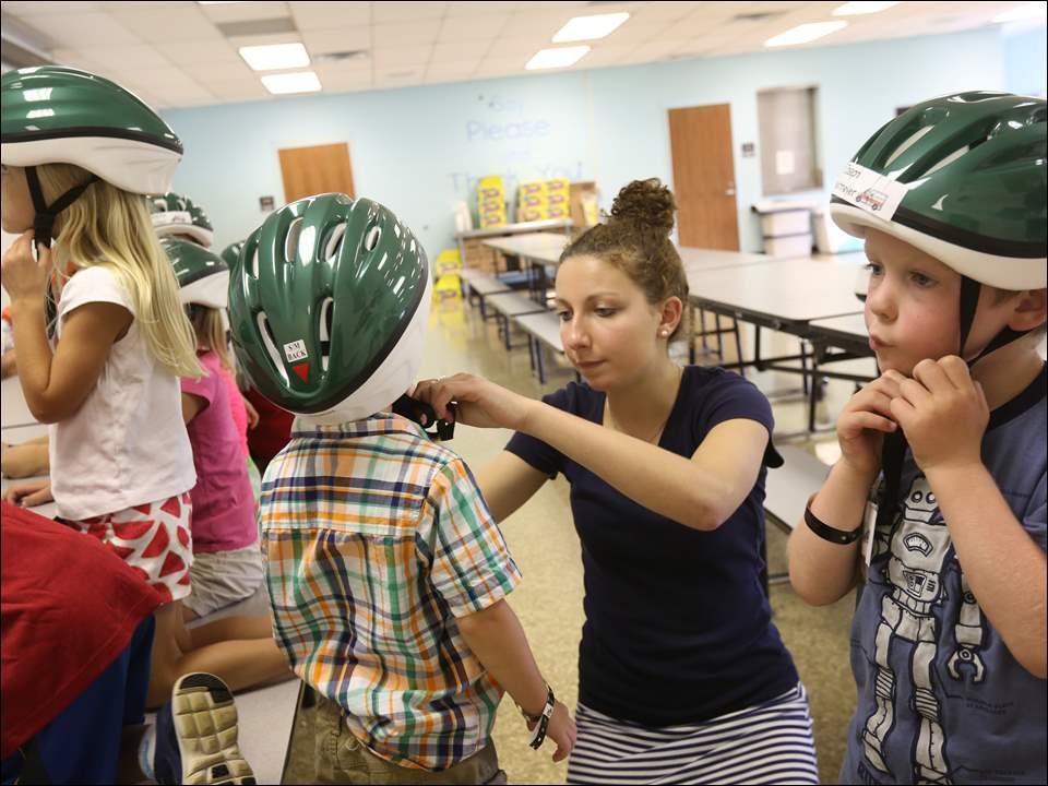 Emily Panzero, center right, helps Christian Fleck-McLain, 5, center left, tighten his helmet while Joseph Westmeyer, 6, right, makes his own adjustments.