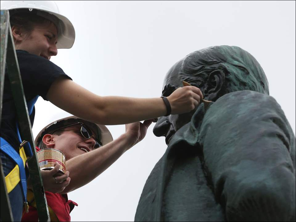 Hannah Yeager, left, and Conor Roberts, right, apply wax after heating the statue of President William McKinley while they work with classmates to restore the sculpture