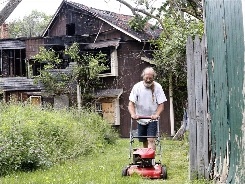 Tim Johnson mows a strip of yard next to his Broadway Street home in South Toledo. The house behind his home, in background, caught fire more than five years ago and is still standing, to his frustration; and the house beside him was tore down after a fire, but the grass is tall.