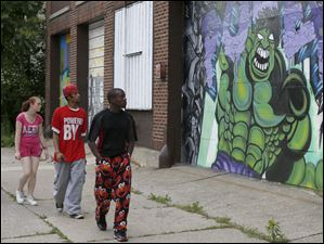 From left: Candace Lainer, 18, AJ Rivers, 27, and Frankie Miles, 22, walk past artwork that masks the ugliness of an abandoned building on Segur Avenue.
