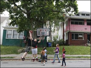 Hunter Elliott, 14, shoots a basket against his brother Nathan Elliott, 12, during a neighborhood basketball game in front of a vacant home on Platt Street.