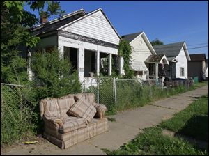 On Sumner Street in South Toledo, this old couch, overgrown greenery, and  an abandoned house are examples of blight.