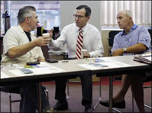 Brian Castro, ombudsman for the U.S. Small Business Administration, center, talks with John Insco of Toledo, left, and Ray Zammit of Oregon on Thursday at the Toledo Regional Chamber of Commerce offices in Toledo. Mr. Castro was in town to advise small business owners on how to get help.