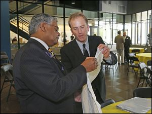 Nagi G. Naganathan, UT professor and dean of the engineering college, left, looks at packing material shown by Sean Hadley, co-owner of H&H Specialities.