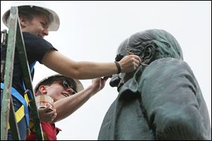 Hannah Yeager, left, and Conor Roberts apply wax after heating the statue of President William McKinley while they work with classmates to restore the sculpture, which is on the south side of the Lucas County Courthouse.