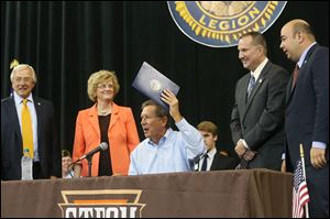 Gov. John Kasich, center, performs a ceremonial signing of House Bill 484  with state and local officials, from left, former Bowling Green State University trustee J. Robert Sebo, BGSU President Mary Ellen Mazey, state Rep. Tim Brown (R., Bowling Green), and state Rep. Cliff Rosenberger (R., Clarksville, Ohio). The law, officially signed last week, changes the state funding formula for two-year colleges to a performance-based model similar to one passed for four-year schools last year.
