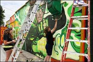 Bowling Green State University students Liz Butterfield, left, and Jamie Scherer, right, work alongside several other students Thursday on a mural on the side of the Green Lantern in South Toledo.