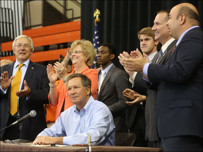kasich12p Surrounded by local school and public officials, including J. Robert Sebo, left, and BGSU President Mary Ellen Mazey, center left, Gov. John Kasich signs House Bill 484, a piece of educational legislation, before a group of hundreds of this year's Buckeye Boys State attendees at Bowling Green State University.