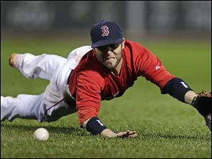 Boston Red Sox second baseman Dustin Pedroia dives to make the play on a ground out by Cleveland Indians' Lonnie Chisenhall.