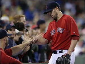 Boston Red Sox starting pitcher John Lackey is congratulated by teammates after he is taken out during the seventh inning.