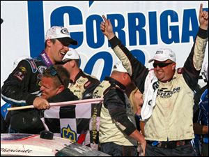 Austin Theriault, with flag, celebrates with his car crew at Victory Lane after winning the ARCA Corrigan Oil 200.
