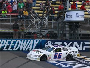 Austin Theriault gets the checkered flag as he crosses the finish line to win the ARCA Corrigan Oil 200 at Michigan International Speedway.