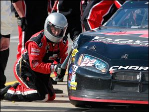 A car crew member adjusts the body of Austin Wayne Self's car.