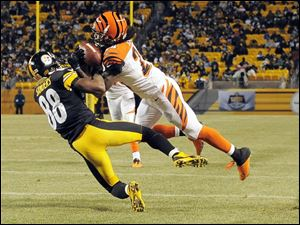 Cincinnati Bengals cornerback Adam Jones intercepts a pass intended for Pittsburgh Steelers wide receiver Emmanuel Sanders in a Sunday night NFL game Dec. 15 in Pittsburgh. NBC's '‍Sunday Night Football' was the highest rated show overall and among viewers 18 to 49.