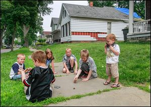 Children play near an abandoned home at 951 Prouty Ave. in South Toledo.
