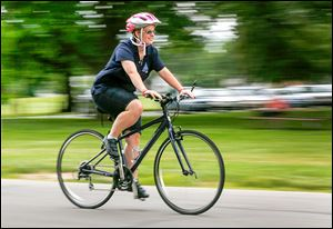 Katie Rupert, who will be a cyclist in the National Special Olympics, rides her bike at the City Park in Bowling Green.