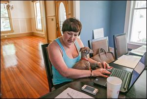 Velvet Bradley works part-time at the dining room table in her home, with her Italian greyhound, Sterling, in her lap, while editing a magazine in Rockmart, Ga. The living room behind her is empty because her house has been foreclosed on and she is in the process of moving out.