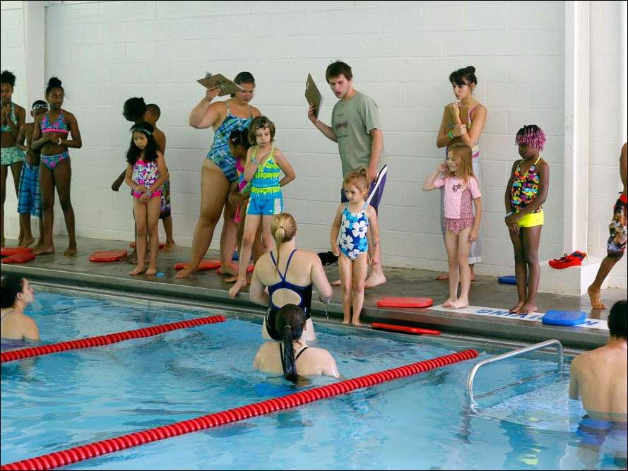 Volunteer swimming instructors organize the first session of students at the edge of the pool during a swimming and safety class sponsored by Wanda Butts.