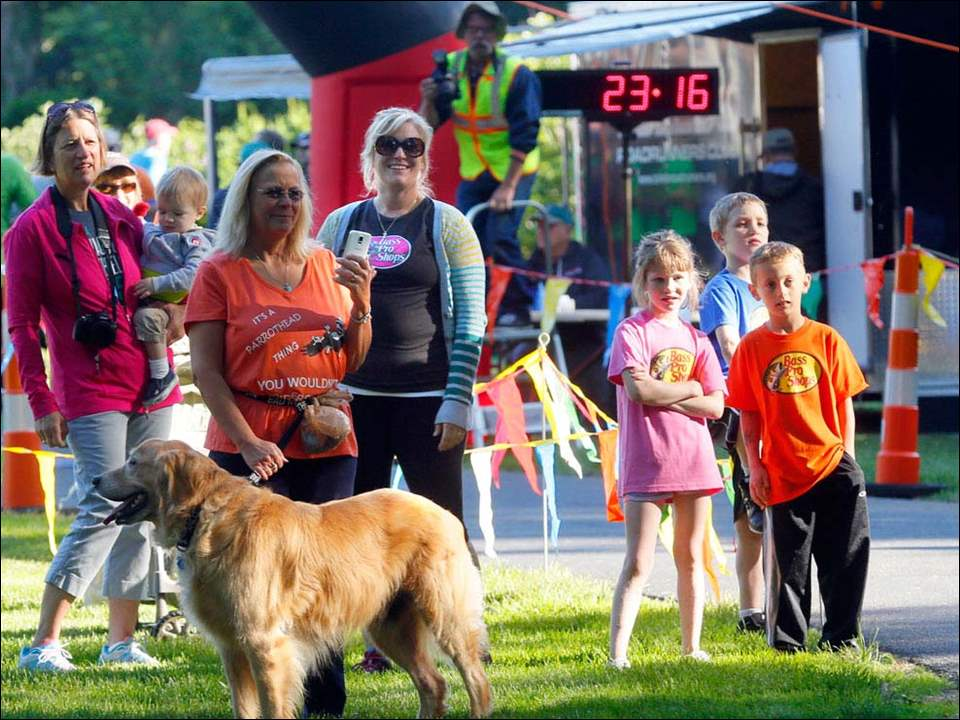 Fans and family wait for runners at the finish line during the 10th Annual Happy Trails 5K run/walk at the Wildwood Preserve.