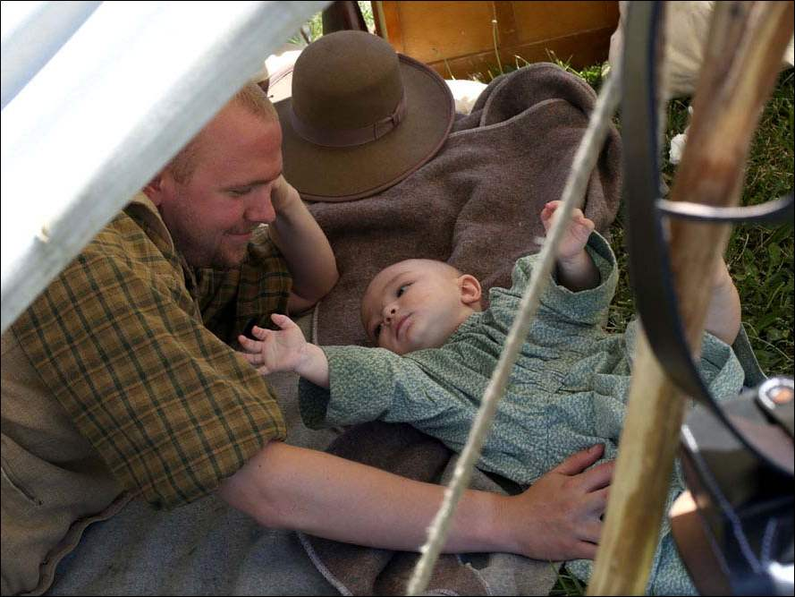 Nate Burgy, of North Toledo, keeps an eye on his seven-month-old son Saxon, from inside their tent in the Confederate camp during this year's Muster on the Maumee.