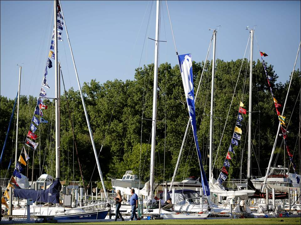 People wander around the sailboats during the Mills Trophy Race Press Party on June 5 at the Toledo Yacht Club.