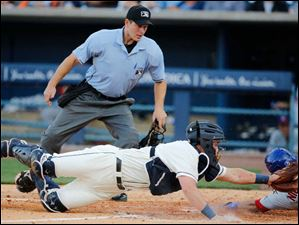Toledo Mud Hens catcher James McCann can't make the tag as Buffalo Bisons' Mike Nickeas scores.