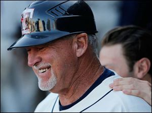 Toledo Mud Hens manager Larry Parrish laughs in the dugout between innings.