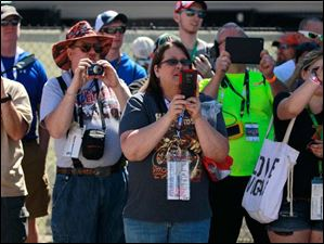 Race fans take photos of Dale Earnhardt Jr. while he's out of his car.