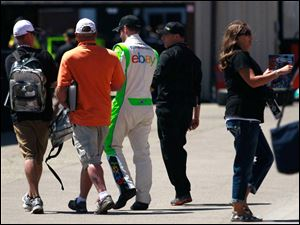 Driver Dale Earnhardt Jr. is surrounded by fans as he walks through the garage area at the Michigan International Speedway.