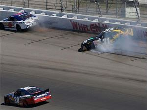 Sam Hornish Jr. races past Trevor Bayne, 6, and Dylan Kwasniewski as they crash into the wall on Turn 2.