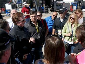 Car owner Richard Childress, left, talks to race fans in front of driver Ty Dillon's garage.