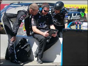 Nationwide driver Brian Scott, left, confers with crew members during qualification.