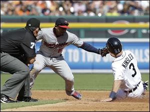 Detroit Tigers' Ian Kinsler steals second base under the tag of Minnesota Twins shortstop Eduardo Escobar.