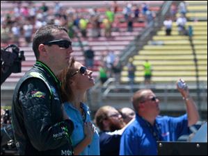Kyle Busch and his wife Samantha Busch look up the the passing jets prior to the start of the race.