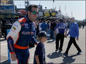 Driver Sam Hornish Jr. stops to pose with a young fan on his way to qualify.