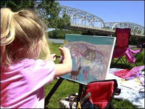 Callie Elder, 4, creates a colorful sky in her painting near the Maumee River.