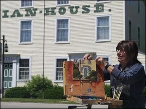 Susan Ritter, an artist based in Perrysburg, removes her finished painting of the Columbian House off her easel.