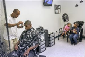 Barber Devon Hands, Sr., talks with Nathaniel Jenkins IV while trimming his hair as Mr. Hands' son Da'Mauri, 2, and stepson Dale Richardson-Bey, 8, play. Groups providing the haircuts say looking good gives men confidence at work and at home.