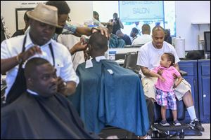Barber Devon Hands, Sr., right, helps his son Da'Mauri, 2, up into a spare chair at Hair Trendz Barbershop on Saturday. Free hair cuts were offered for fathers and sons to celebrate Father's Day.