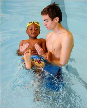 Volunteer swimming instructor William Knight, 16,  eases pupil Octavius Harris, 5 from Toledo, into the water.