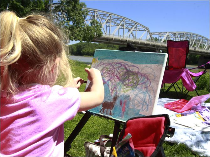 nbrs openair09p colorful sky Callie Elder, 4, creates a colorful sky in her painting near the Maumee River during the open air art festival.