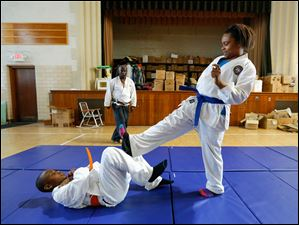 Iesha Matthews, 12, practices with Timothy Hicks, 11, as instructor Lowell Cherry, Jr., watches.