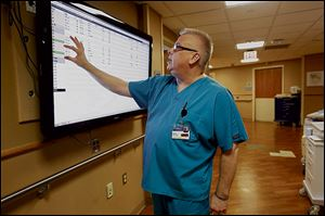 Kevin Cischke examines the board that announces where patients are located in order to see if a new patient has come into the emergency room.