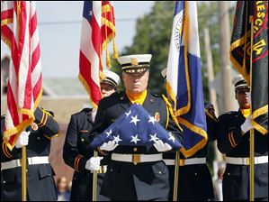 Jeff Koenigseker, a Toledo firefighter and honor guard commander, carries the flag.