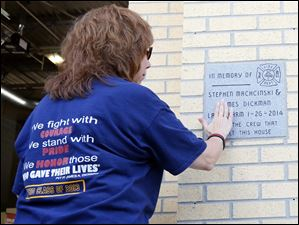 Gale Dickman, James Dickman's aunt, touches the memorial plaque.