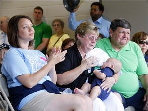 Fallen Toledo firefighter Private James Dickman'€™s wife, Jamie Dickman, left, mother Linda Dickman, who is holding grandson James Dickman's son Grant, and Greg Dickman, right, react to the station being dedicated to their son and fallen firefighter Stephen Machinski.