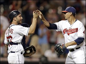 Cleveland Indians catcher George Kottaras, left, congratulates relief pitcher Carlos Carrasco after struck out Los Angeles Angels' Josh Hamilton for the final out.