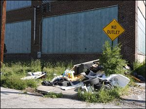 Trash is dumped in front of a boarded-up  building on Castle Drive between Maplewood and Glenwood avenues in Toledo.